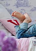 Kleines Kind liegt barfuß auf Bett