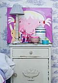Bedside lamp and child's picture on bedside table against wallpapered wall