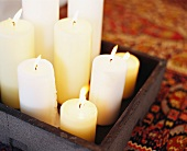 Burning candles in assorted sizes on a wooden tray