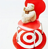 Teddy bear on a red 'Bauhaus' shell chair