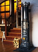 Old cylindrical cast iron stove next to stairs in a living room with an open door