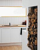 Firewood storage in a wall niche next to a modern kitchen