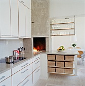 Modern kitchen with white cabinet front and fireplace