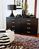 Carpet with circular pattern in front of a chest of drawers made of dark wood and a black table lamp