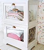 Table linens and pillows stacked in a glass-front cabinet
