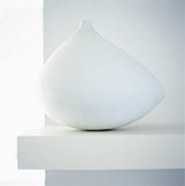 White ethnic vase on a shelf