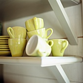 Yellow espresso cups on a shelf