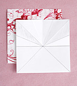 Series of photos showing steps for folding a paper flower from red and white patterned origami paper
