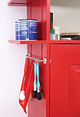 Shelves and hook rail attached to outer wall of red tool cabinet provide extra storage space for paintbrushes and tins of paint