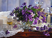 Purple spring bouquet in glass vase next to various glass containers on wooden shelf