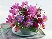 Purple posy in ceramic vase on saucer and tray