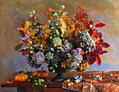 Autumnal bouquet and ornamental squashes on wooden table