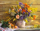 Colourful bouquet in ceramic vase and apricots on shelf against wooden wall
