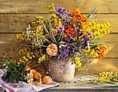 Bunter Blumenstrauss in Tonvase und Aprikosen auf Ablage vor Holzwand