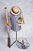 Tailor's dummy with waistcoat and garden tools