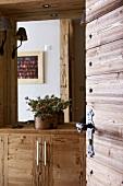 View of rustic, wooden sideboard through open interior door