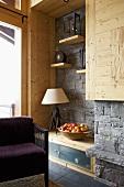 Rustikal moderne Zimmerecke mit grauer Natursteinwand und violettem Sessel