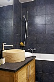 Modern bathroom with stone basin on washstand and dark grey wall tiles