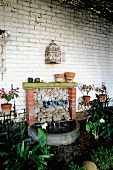 Homemade fountain in garden against whitewashed brick wall with antique decorative elements of curved wire
