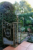 Old, decorative iron gate on wide steps and view into sheltered, Romantic terrace garden