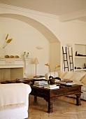 Antique coffee table and white sofas in front of open fireplace in arched surround