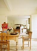 Rustikaler Essplatz mit Kunstobjekt auf Tisch und Blick durch geöffnete Flügeltüren in Küche