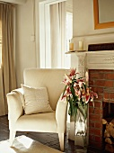 Elegant armchair with white cover and bouquet of lilies next to brick fireplace