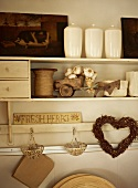 Vintage kitchen shelves with white ceramic storage jars and heart-shaped wicker wreath