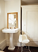 Delicate metal chair painted white next to antique pedestal washstand in corner of bathroom