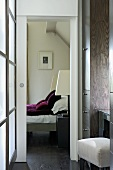 Anteroom with fitted wardrobe and view of modern bed through open sliding door