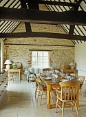 Rustic dining area in open-plan room with stone walls and roof timbers