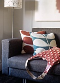Scatter cushions with abstract floral covers and retro handbag on sofa