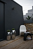 Chrome planters and designer garden furniture against black wall on terrace