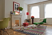 Green designer armchair with matching footstool on rug in room with fireplace