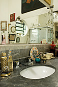 Large wall-mounted mirror above marble washstand in bathroom