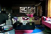 Black Venetian plaster walls, colourful silk carpet, sofas and black coffee table in elegant living room