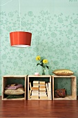 Wooden boxes with stacked books and orange hanging lamp in front of floral wall paper