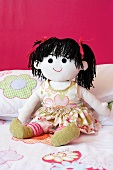 Hand-made rag doll with black wool pigtails against bright pink wall
