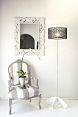 Vintage look, upholstered armchair next to a designer lamp in front of a wall with a mirror