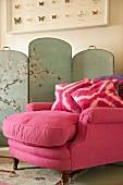 Antiker Polstersessel mit rosa Samtbezug und Kissen vor bemaltem Paravent mit chinesischem Motiv