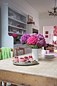 Pink and violet bouquet in ceramic jug and tray of desserts on rustic dining table