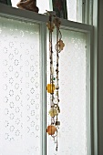 Necklace with flower motif hanging in front of window