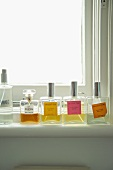 Various flagons of perfume on window sill