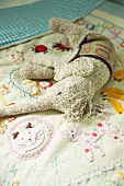 Soft toy on embroidered child's bedspread