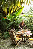 Woman preparing food on terrace table in tropical surroundings