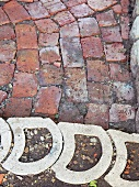 Curved, hollow concrete pavers edging a section uneven brick pavers