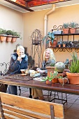 Coffee break in a courtyard - two laughing ladies at a garden table with a collection of cacti and iron wire wall shelves with plant pots