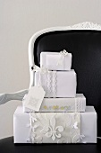 Presents wrapped in white paper on a black chair