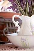 Close up of a porcelain pitcher with lavender flowers