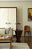 Biedermeier-style side table with fifties table lamp in modern living room
